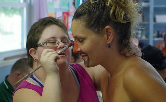 Activité de maquillage au camp Garagona: un campeur maquille un employé